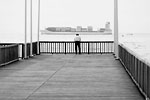 Le Havre - Lonely man on the wooden pier peering at a cargo